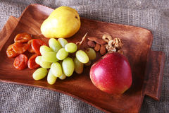 Fresh organic fruits on wood Serving tray. Assorted apple, pear, grapes, dried fruits and nuts. Stock Photography