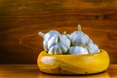 Garlic in a hand turned wooden bowl on a reclaimed hard wood background. Royalty Free Stock Photo