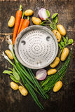 Fresh organic garden vegetables around empty colander bowl on dark rustic wooden background Stock Photo