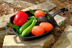 Fresh organic garden vegetables in pan on a stone stock images