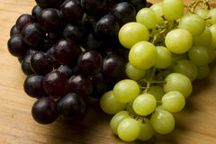 Fresh organic grapes. Fresh red and white organic grapes on a wooden table Stock Images