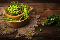 Fresh organic green peas on a wooden background.Rustic style. Fresh organic green peas on wooden background.Rustic style Stock Images
