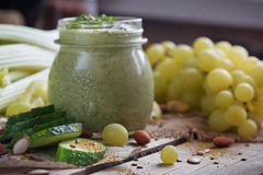 Fresh organic green smoothie with cucumber, parsley, grapes and celery. On wooden background Stock Photography