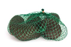 Fresh organic hass avocados in a green string bag on a white background isolated, healthy food concept, copy space royalty free stock photos