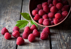 Fresh organic healthy raspberry with mint leaves. In clay dish on vintage wooden table background. Rustic style and natural light. Dark food photo Stock Images
