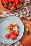 Fresh organic home growth strawberries on wooden table in plate Stock Photography