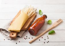 Fresh organic homemade spaghetti pasta with bottle of tomato sauce and wooden spatula and basil leaf on wooden board background. Fresh organic homemade stock photo
