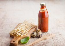 Fresh organic homemade spaghetti pasta with quail eggs with bottle of tomato sauce and wooden spatula and basil leaf on wooden. Board background. Classic stock photography
