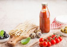 Fresh organic homemade spaghetti pasta with quail eggs and fresh tomatoes with bottle of tomato sauce and wooden spatula and basil. Leaf on wooden board stock images