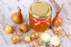 Fresh organic honey in glass jar and onions on wooden background, healthy nutrition and strengthening immunity Royalty Free Stock Photography