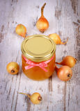 Fresh organic honey in glass jar and onions on wooden background, healthy nutrition and strengthening immunity Stock Images
