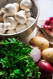 Fresh organic ingredients for preparing healthy vegetarian meal mushrooms in colander, potatoes, onion, parsley Royalty Free Stock Photo
