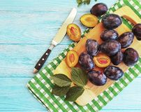 Fresh organic juicy dessert gourmet slice plum natural autumn delicious on a table , blue wooden background, towel. Fresh organic plum slice on a blue wooden royalty free stock image