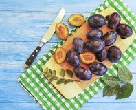 Fresh organic juicy dessert gourmet slice plum vitamin natural autumn delicious on a table , blue wooden background, towel. Fresh organic plum slice on a blue royalty free stock photography