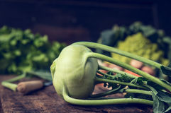 Fresh organic kohlrabi on rustic kitchen table with garden vegetables. Over wooden background Stock Photo