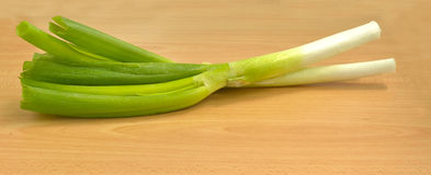 Fresh organic leek. Farm fresh organic leek, spring salad ingredient on wooden table, selective focus Stock Photos