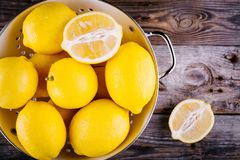 Fresh organic lemons in a colander on a wooden background. Top view Stock Photography