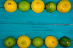 Fresh organic lemons and limes on wooden background Royalty Free Stock Images
