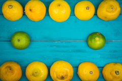 Fresh organic lemons and limes on wooden background Royalty Free Stock Image