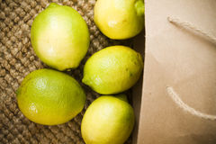 Fresh organic lime fruits. Spilling out of a brown paper shopping bag Stock Images