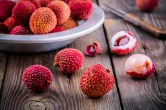 Fresh organic lychee fruit in a bowl on wooden background Royalty Free Stock Image