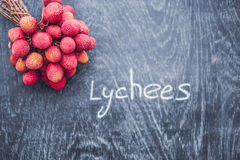 Fresh organic lychee fruit and lychee leaves on a rustic wooden Stock Photos