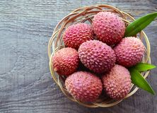 Fresh organic lychees in a basket on old wooden background.Exotic tropical lychee fruits. Stock Photo