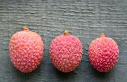 Fresh organic lychees on old wooden background.Exotic tropical lychee fruits pattern.Flat lay,top view. Stock Photo