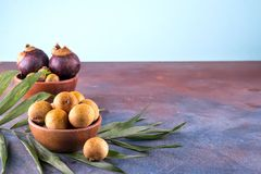 Fresh organic lychees with palm leaf in a bowl on stone background. Raw diet or vegan food concept. Fresh organic lychees with palm leaf in a bowl on stone royalty free stock images