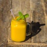 Fresh organic mango shake in glass mug on wooden table, close up. Fresh organic mango smoothie in glass mug on wooden table, close up Stock Image