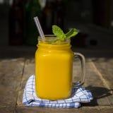 Fresh organic mango shake in glass mug on wooden table, close up. Fresh organic mango smoothie in glass mug on wooden table, close up Stock Photo