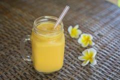 Fresh organic mango shake in glass mug on wooden table, close up. Fresh organic mango smoothie in glass mug on wooden table, close up Stock Photos