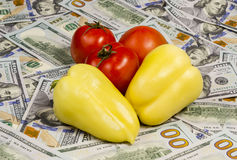 Fresh Organic and money. Fresh Fresh organic vegetables tomatoes and pepper on a background of hundred dollar bills Royalty Free Stock Photo