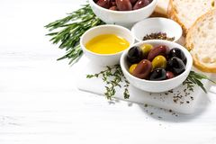 Fresh organic olives, spices and bread on white wooden table Royalty Free Stock Image