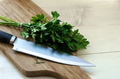 Fresh organic parsley with knife on wooden cutting board. Stock Photo