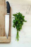 Fresh organic parsley with knife on wooden cutting board. Stock Photos