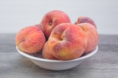 Fresh, organic peaches in white bowl, ,on wooden table royalty free stock image