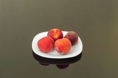 Fresh Organic Peaches in a White Plate. Fresh Organic Peaches Served in a White Plate Royalty Free Stock Photography