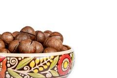 Fresh organic peeled macadamia nuts in ceramic bowl isolated on white stock image