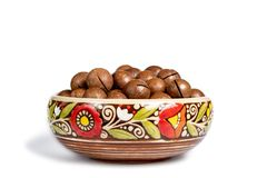 Fresh organic peeled macadamia nuts in ceramic bowl isolated on white stock photography