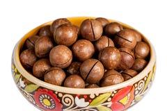 Fresh organic peeled macadamia nuts in ceramic bowl isolated on white royalty free stock image