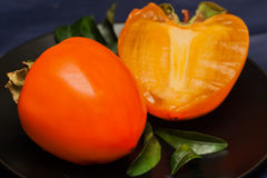 Fresh organic persimmon fruit cut in half on dark background. Concept for healthy food, vegan or raw diet Stock Photos