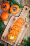 Fresh organic persimmon with slices on wooden board Stock Image