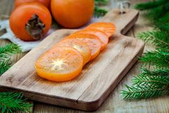 Fresh organic persimmon with slices on wooden board Royalty Free Stock Photography