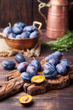 Fresh organic plums in copper bowl and on rustic wooden cutting board. Stock Images