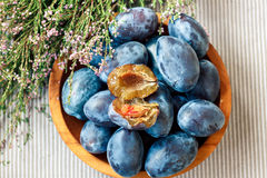 Fresh organic plums in wooden bowl. Closeup Stock Images