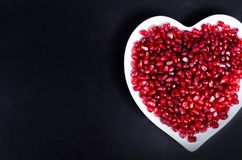 Fresh organic pomegranate seeds in white heart shaped bowl. Free space for your text. Fresh organic pomegranate seeds in white heart shaped bowl. Free space for Royalty Free Stock Photo