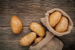 Fresh organic potatoes in hemp sake bags on rustic wooden backgr Royalty Free Stock Image