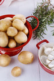 Fresh organic potatoes, rosemary and garlic over white wooden ba Royalty Free Stock Image