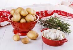 Fresh organic potatoes, rosemary and garlic over white wooden ba. Fresh organic potatoes in a red collander, rosemary and garlic over white wooden background stock photos